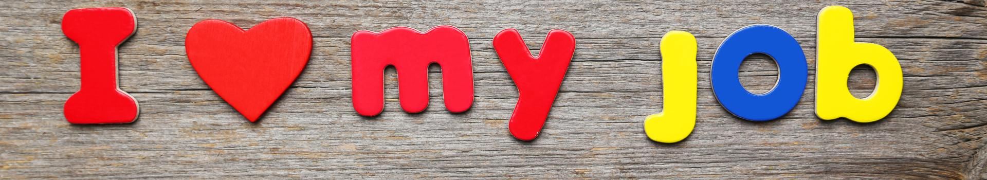 Letters spelling 'I love my job' on wood background